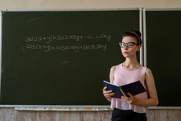 Nauczyciel napisany na tablicach szkolnych formuł matematycznych. algebra