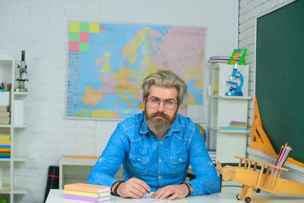 Nauczyciel nauczycieli dzień z powrotem do szkoły nauczyciel września przygotowuje lekcje w klasie nauczyciel mężczyzna