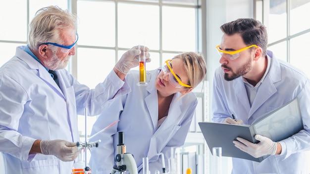 Nauczyciel nauk ścisłych i zespół studentów pracujących z chemikaliami w laboratorium