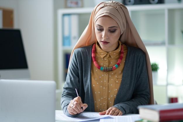Nauczyciel noszący hidżab. stylowy muzułmański nauczyciel noszący hidżab czuje się zajęty poprawianiem testów