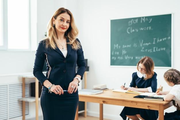 Nauczyciel patrząc na aparat stojący w klasie.