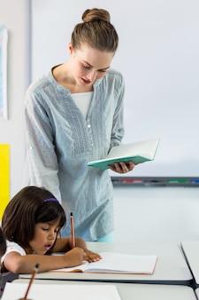 Nauczyciel patrzeje uczni pisze na książce