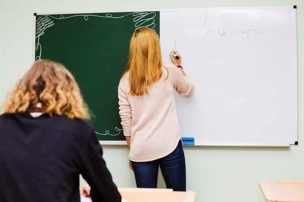 Nauczyciel pisze na tablicy dla ucznia