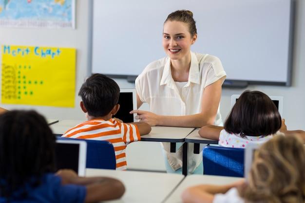 Nauczyciel pokazuje cyfrową pastylkę z dziećmi