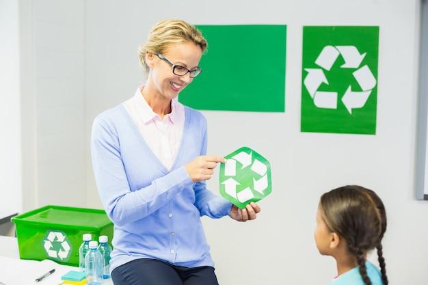 Nauczyciel pokazuje recykling logo uczennicy