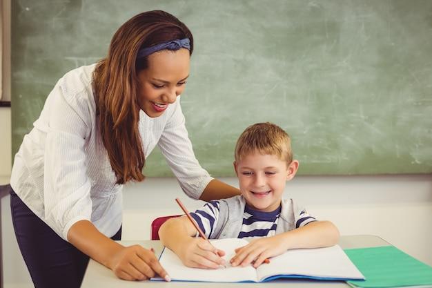 Nauczyciel pomaga chłopcu w odrabianiu lekcji w klasie