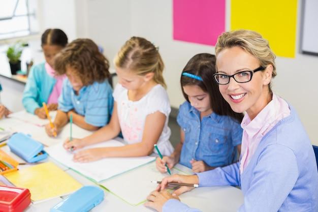 Nauczyciel pomaga dzieciom w odrabianiu lekcji w klasie
