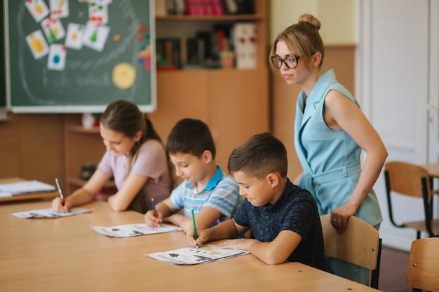 Nauczyciel pomaga dzieciom w szkole pisać test w klasie. edukacja, szkoła podstawowa, nauka i