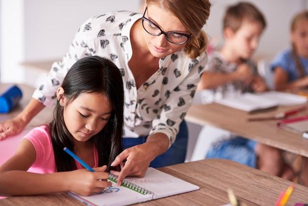Nauczyciel pomaga dziewczynie w odrabianiu prac domowych