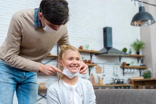 Nauczyciel pomaga dziewczynie założyć maskę medyczną