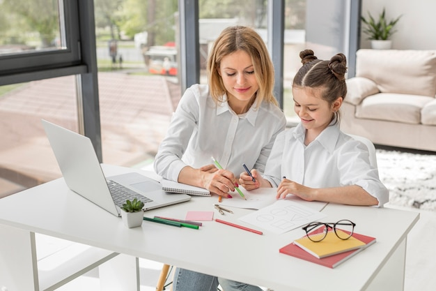 Nauczyciel pomaga jej córce studiować przy biurkiem