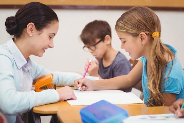 Nauczyciel pomaga małej dziewczynce podczas lekcji