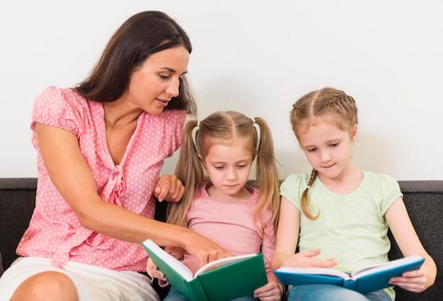 Nauczyciel pomaga małym dziewczynom w czytaniu nowej lekcji