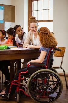 Nauczyciel pomaga niepełnosprawnemu uczniowi