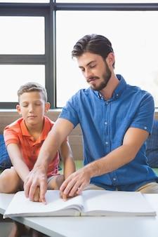 Nauczyciel pomaga niewidomemu uczniowi w bibliotece
