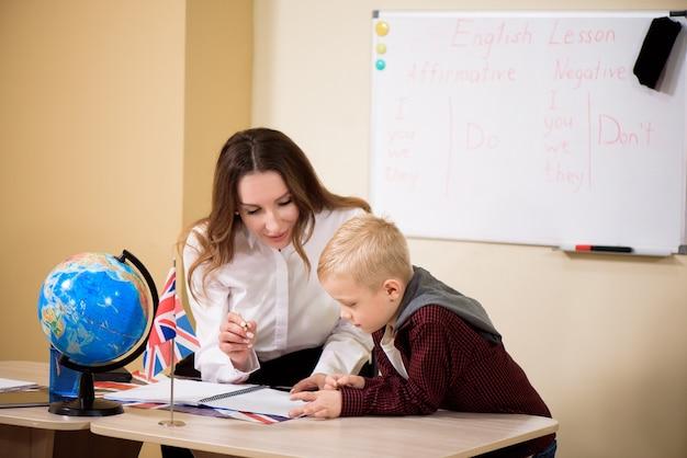 Nauczyciel pomaga uczniowi z czytania przy biurku.