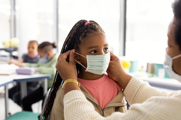 Nauczyciel pomaga uczniowi założyć maskę medyczną