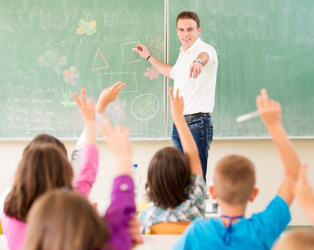 Nauczyciel pracuje z dziećmi w szkolnej klasie