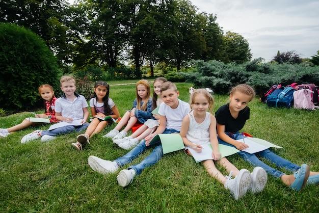 Nauczyciel prowadzi klasę dzieci w parku na świeżym powietrzu. powrót do szkoły, nauka w czasie pandemii.
