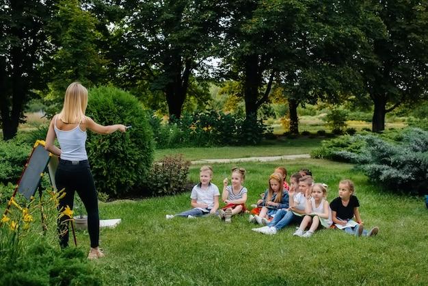 Nauczyciel prowadzi klasę dzieci w parku na świeżym powietrzu
