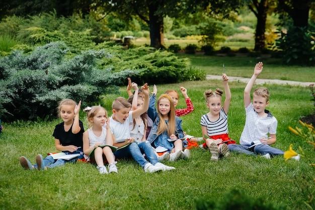 Nauczyciel prowadzi klasę dzieci w parku plenerowym. powrót do szkoły, nauka podczas pandemii.