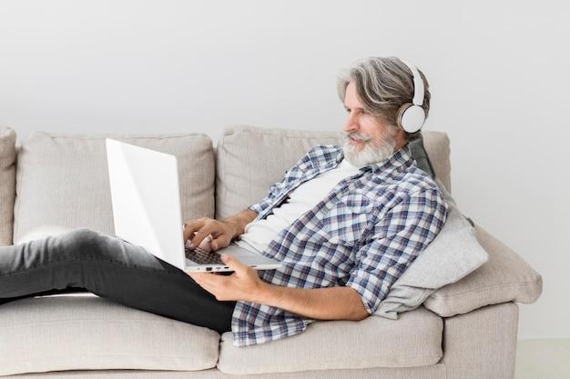 Nauczyciel przebywa na kanapie z laptopem