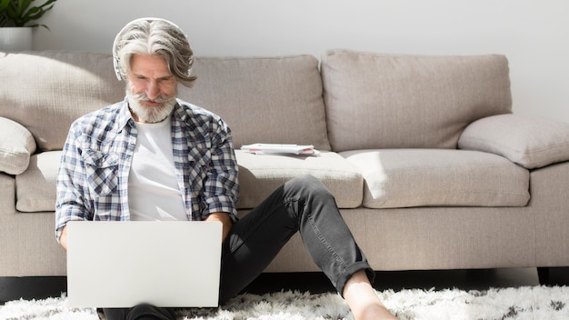 Nauczyciel przebywa na podłodze patrząc na laptopa