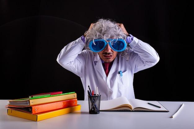 Nauczyciel przedmiotów ścisłych w białym fartuchu zdesperowany w białym fartuchu przykłada ręce do włosów