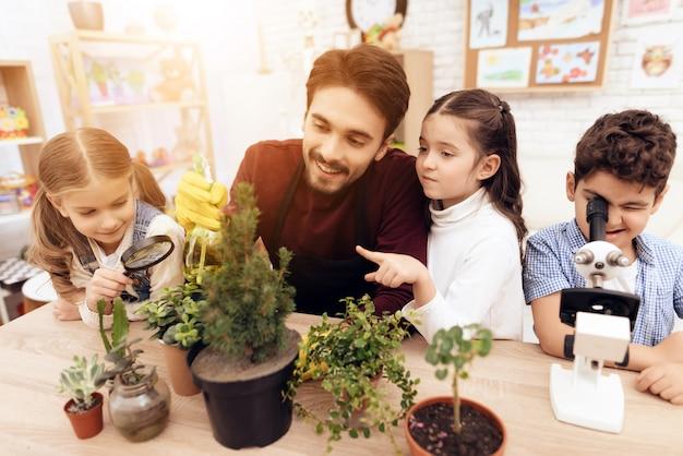 Nauczyciel przedszkola uczy opryskiwania roślin.
