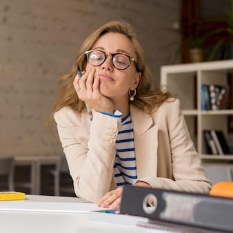 Nauczyciel przy biurku zmęczony