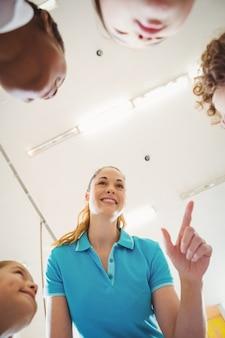 Nauczyciel rozmawia z kilkoma uczniami