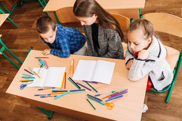 Nauczyciel siedzący między uczniami