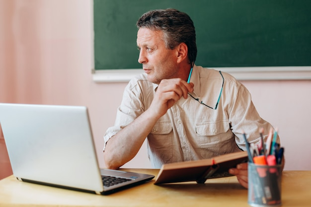 Nauczyciel siedzący z podręcznikiem i laptopem odwraca głowę na bok