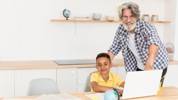 Nauczyciel siedzi obok chłopca na laptopie