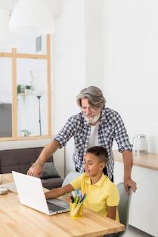 Nauczyciel siedzi obok ucznia na laptopie