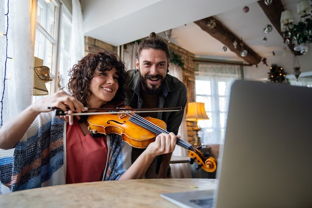 Nauczyciel skrzypiec mężczyzna pomaga studentce w domu