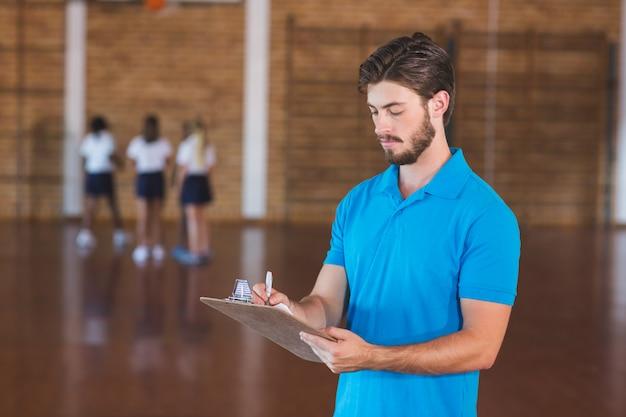 Nauczyciel sportowy pisze w schowku