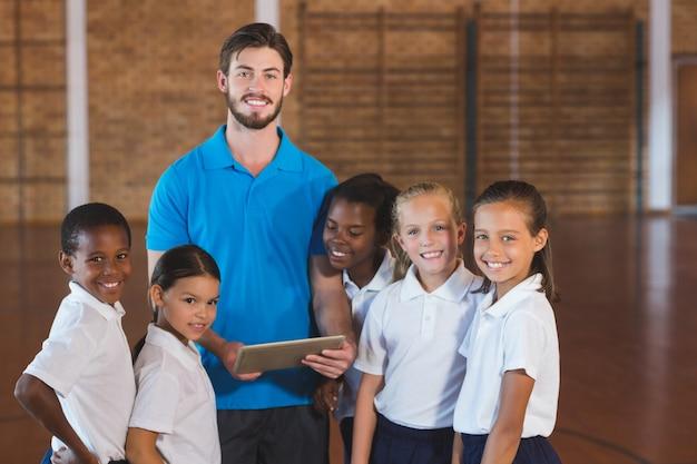 Nauczyciel sportu i dzieci w szkole za pomocą cyfrowego tabletu na boisku do koszykówki