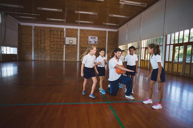 Nauczyciel sportu uczy dzieci w wieku szkolnym gry w koszykówkę