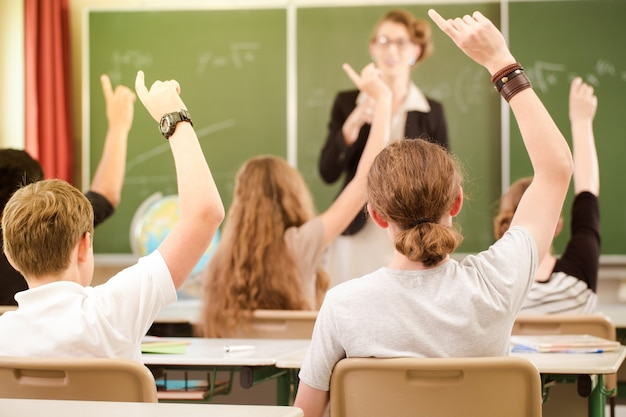 Nauczyciel stoi podczas lekcji przed tablicą i edukuje uczniów, którzy powiadamiają i uczą się w klasie