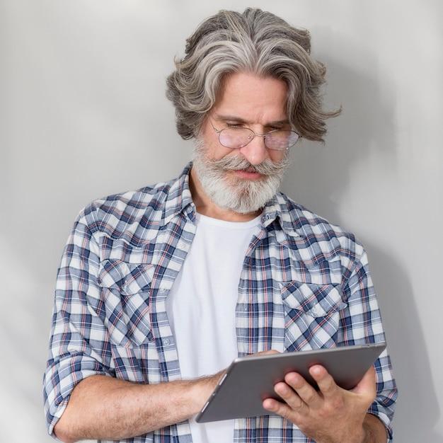 Nauczyciel stojąc i trzymając tablet