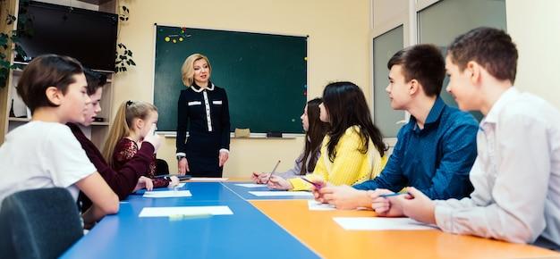 Nauczyciel stojący przed klasą i zadający pytania. koncepcja szkoły.