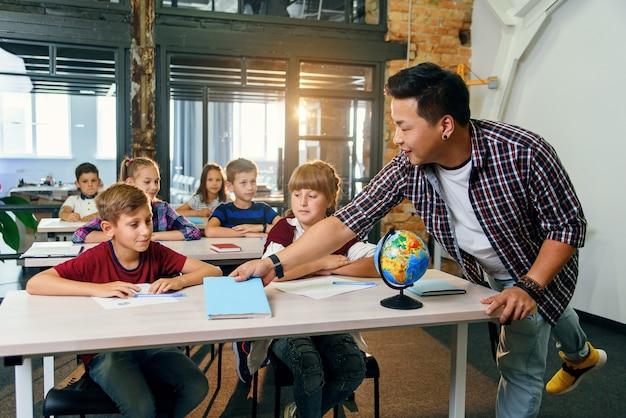 Nauczyciel szkoły podstawowej kładzie zeszyty na biurkach uczniów do nauki. nowoczesna inteligentna szkoła.