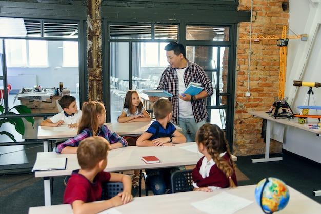 Nauczyciel szkoły podstawowej kładzie zeszyty na biurkach uczniów do nauki.
