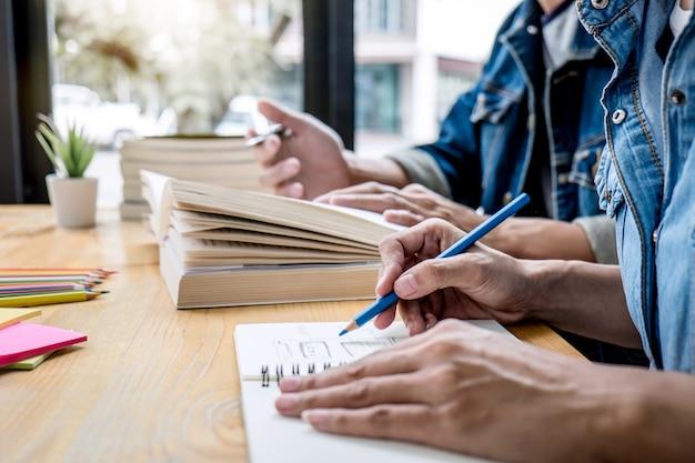 Nauczyciel szkoły średniej lub grupa studentów college'u siedzących przy biurku w bibliotece, studiujący i czytający, odrabiający lekcje i ćwiczący lekcję przygotowujący egzamin do wejścia, edukacji, nauczania, koncepcji uczenia się