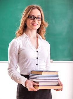 Nauczyciel trzyma książki w klasie.
