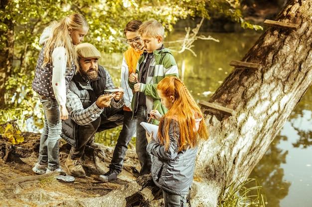 Nauczyciel uczący zainteresowanych uczniów w lesie w słoneczny jesienny dzień
