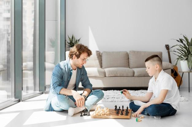 Nauczyciel uczy chłopca, jak grać w szachy długi widok
