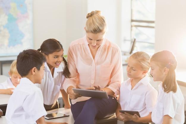 Nauczyciel uczy dzieci na cyfrowym tablecie