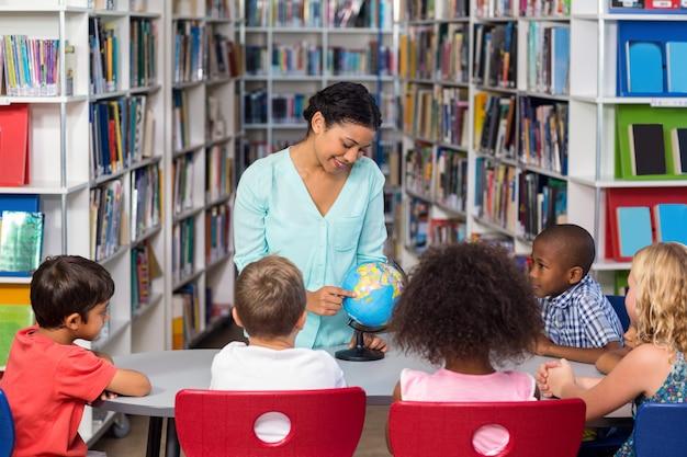 Nauczyciel uczy dzieci używa kulę ziemską na stole